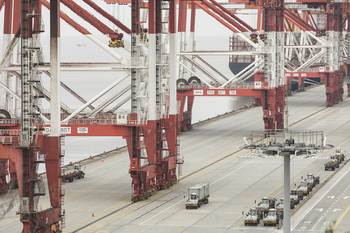 Container trucks move past gantry cranes at the Yangshan Deep Water Port in Shanghai. Photo: VCG