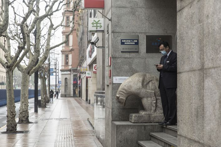 An employee stands outside of a bank in Shanghai. Photo: Bloomberg
