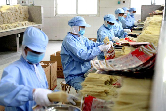 Staff pack rice flour in Ganzhou, Jiangxi province. Photo: VCG