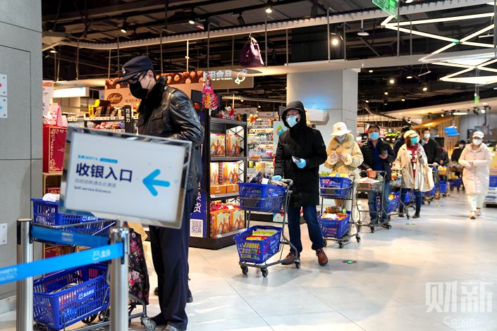 Shoppers queue in a supermarket in Wuhan, Hubei province, on Feb. 12. Photo: Ding Gang/Caixin