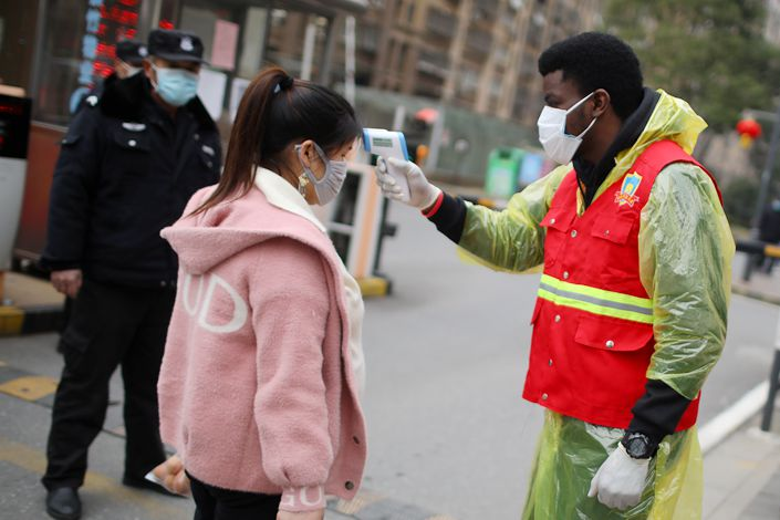 An international student from Nigeria volunteering in Nanjing takes the temperature of people going in and out of a residential community. Photo: China News Service