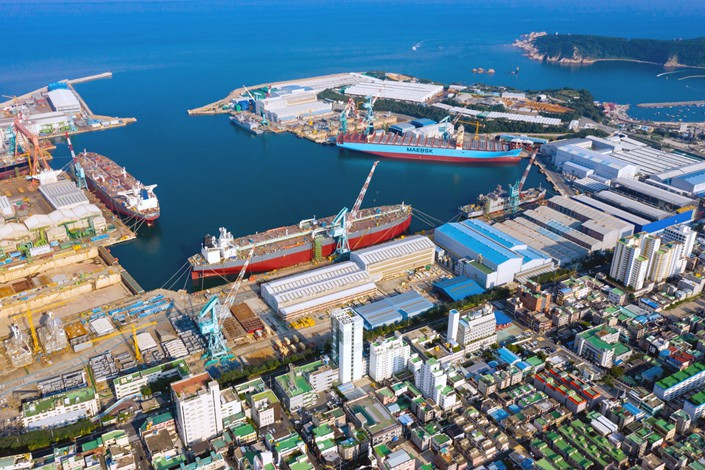 Residential houses and apartment buildings stand as ships sit docked and under construction at the Hyundai Heavy Industries Co. shipyard in the background in this aerial photograph taken above Ulsan, South Korea, on Aug. 4, 2019. Photo: Bloomberg