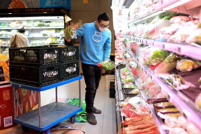 A worker restocks the produce shelves at a supermarket in Beijing on Feb. 10. Photo: IC Photo
