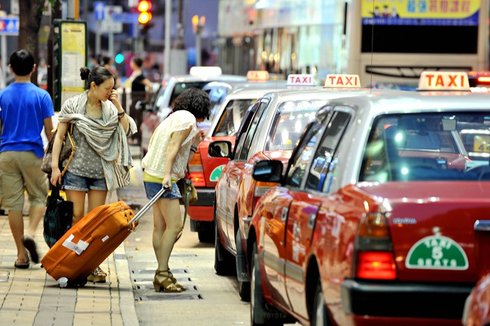 Two women talk with a taxi driver on the street in Hong Kong on June 28. Photo: IC Photo
