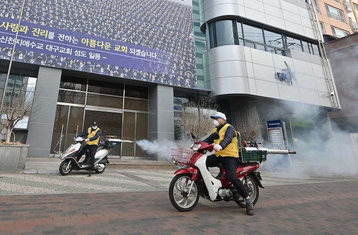 South Korean health officials spray disinfectant in front of the Daegu branch of the Shincheonji Church of Jesus in the southeastern city of Daegu on February 21. Photo: Bloomberg