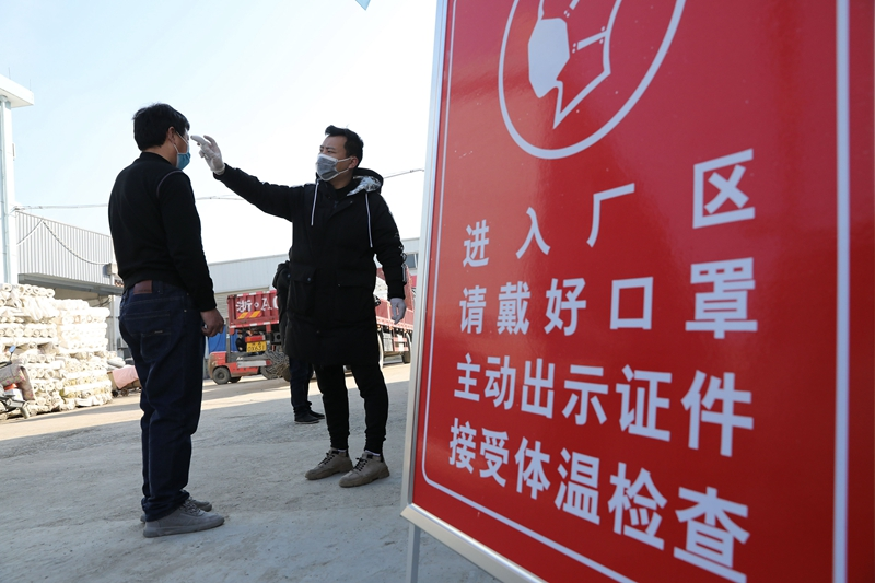 A staffer at a Zhejiang factory tests workers' body temperatures before they enter the plant.