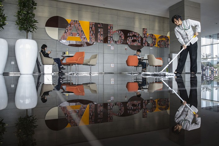 An employee mops the floor in a building lobby at the Alibaba headquarters in Hangzhou on Oct. 13, 2015. Photo: Bloomberg