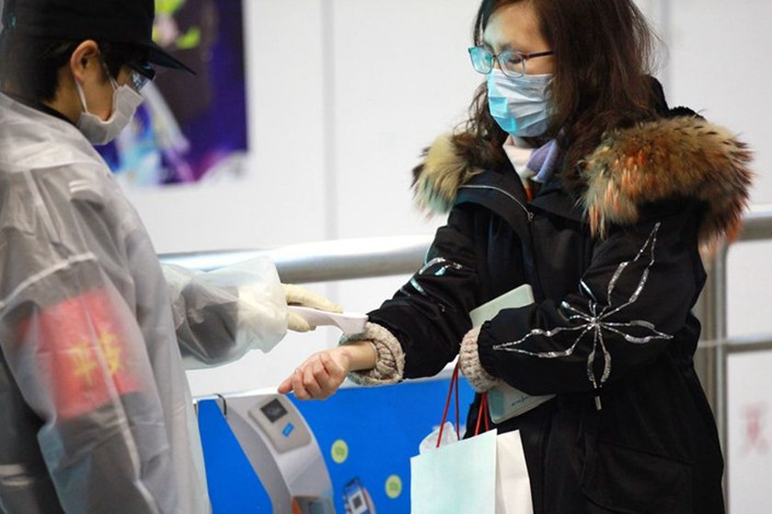 A commuter gets her temperature taken when entering the subway in Nanjing, East China's Jiangsu province, on Feb. 19. Photo: IC Photo