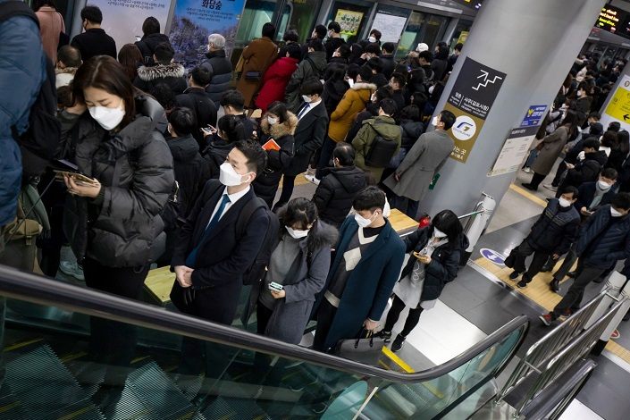 People wearing protective masks ride an escalator inside a subway in Seoul. Photo: Bloomberg