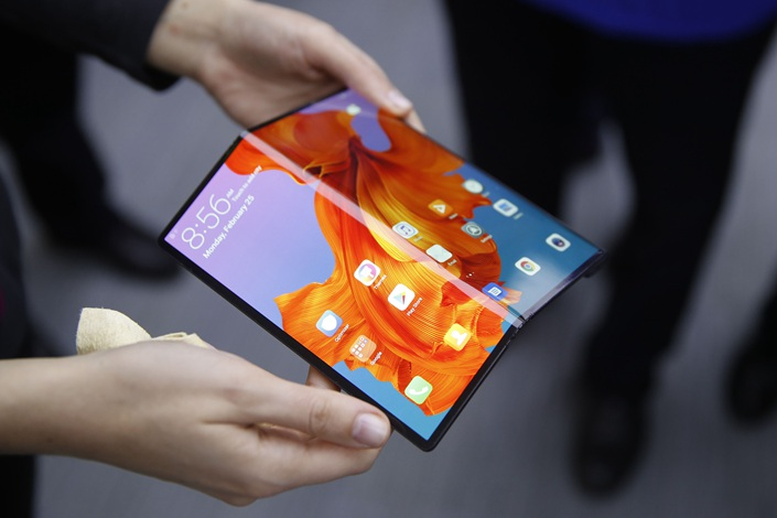 An employee demonstrates a Mate X foldable 5G mobile device at the Huawei Technologies Co. pavilion on the opening day of the MWC Barcelona in Barcelona