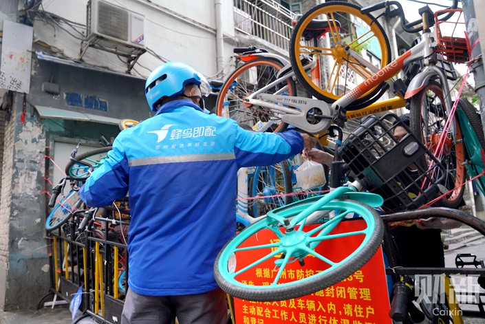 Shared bikes block the entrance of a street in Guangzhou's Liwan district. Photo: Liang Yingfei/Caixin