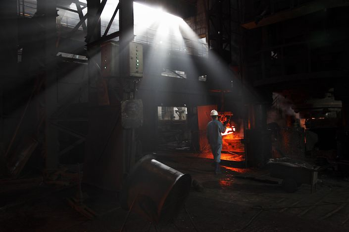 Workers operate on the old assembly line that was built in the 1960s to make train carriage wheels at Ma Steel in Maanshan. Photo: Bloomberg