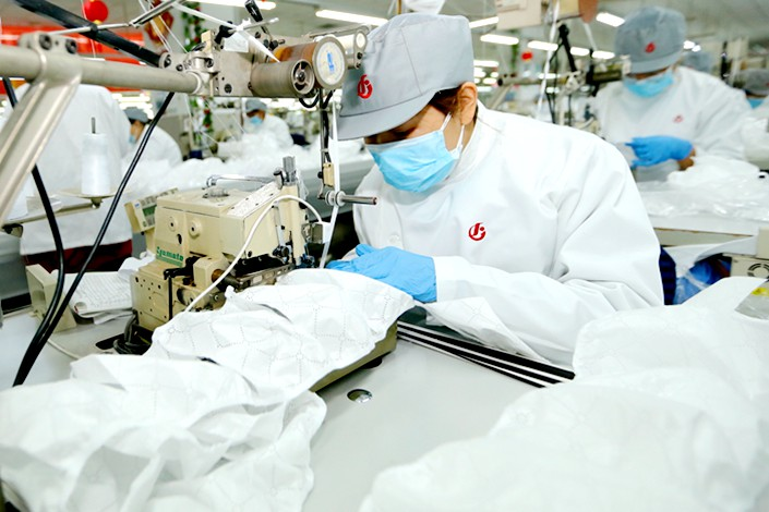 Garment manufacturers turn their hands to making protective clothing in Qingdao, Shandong province, on Feb. 19. Photo: IC Photo