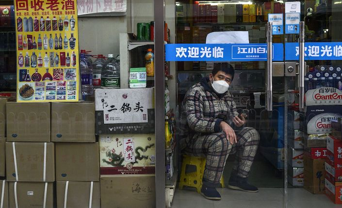 A shopkeeper wearing mask is waiting for customers at a liquor store in Beijing on February 25. Photo: Bloomberg