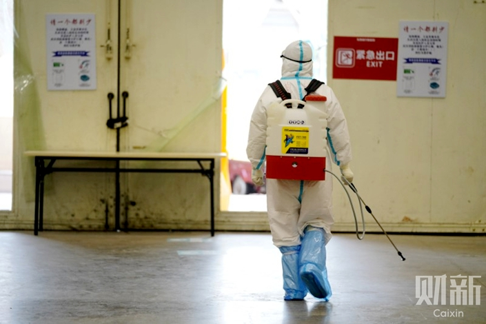 A medical worker disinfects the ground of a makeshift hospital converted from a cultural complex in Wuhan, the epicenter of the coronavirus outbreak, on Feb. 21. Photo: Ding Gang/Caixin