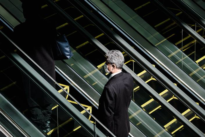 A man wearing a mask rides an escalator in Nagoya, Japan. The Japanese government is considering emergency legislation to deal with the growing global coronavirus outbreak. Photo: IC Photo