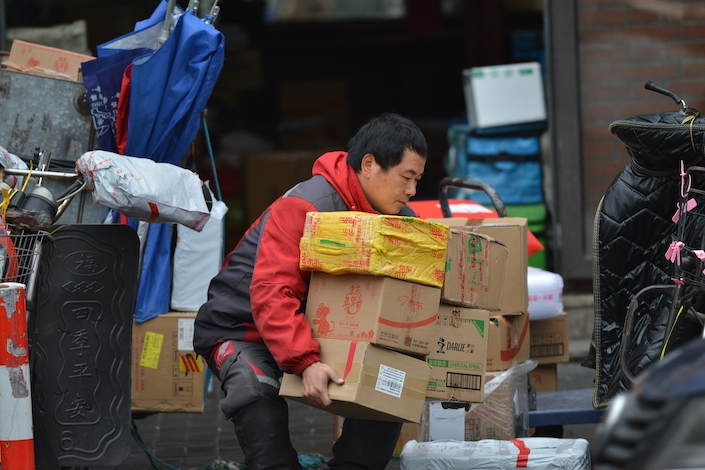 A delivery worker carrying packages. Photo: VCG