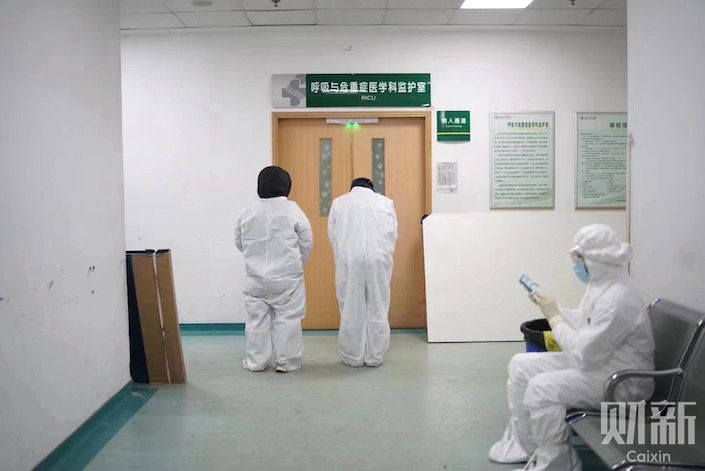 Li Wenliang's colleagues wait outside the ICU while he was in a critical condition. Photo: Ding Gang/Caixin