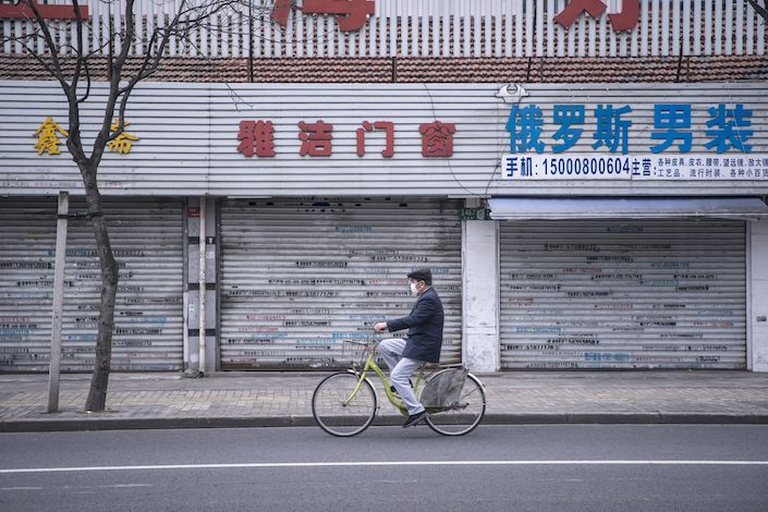 A man wearing a protective mask rides a bicycle past shuttered stores in Shanghai. Photo: Bloomberg