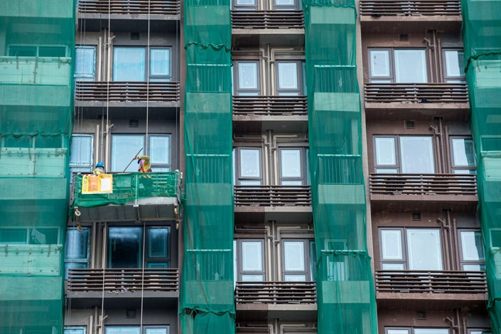 Worker labor on a construction platform at a residential building site in the Yuen Long district of the New Territories in Hong Hong on July 23, 2019. Photo: Bloomberg