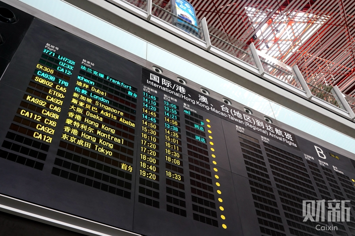 The usually full arrivals board at Beijing Capital International Airport on Thursday. Photo: Caixin