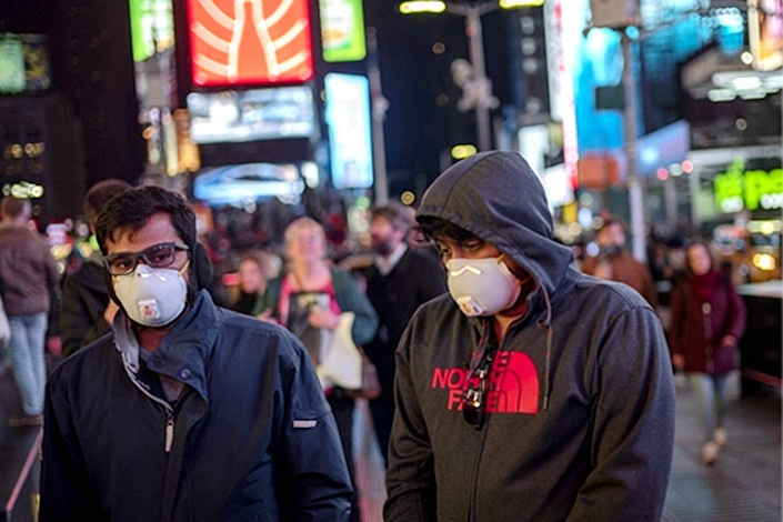 People wearing face masks walk in New York City's Times Square on March 7. Photo: Xinhua
