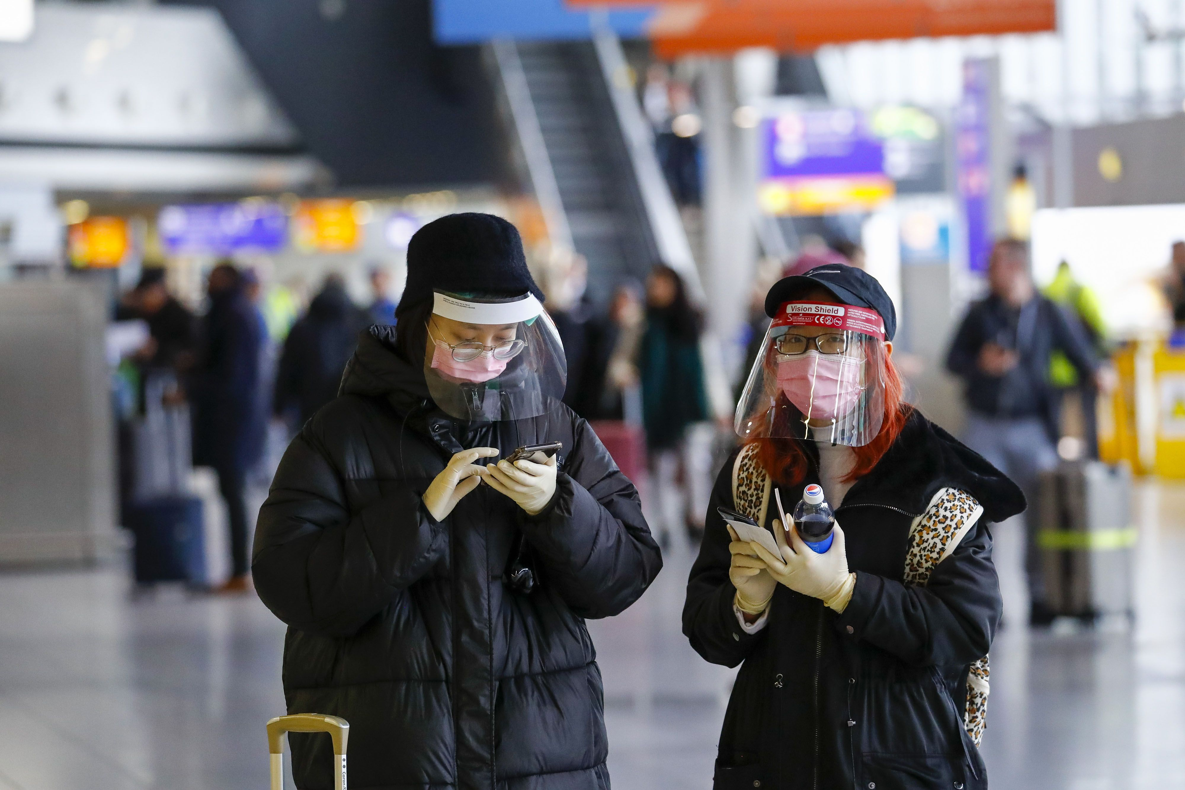 Travelers wear face masks and protective facial visors at Frankfurt Airport. Photo: Bloomberg