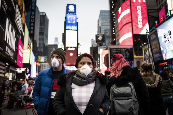 Pedestrians wearing masks walk through the Times Square of New York on March 12. Photo: Bloomberg