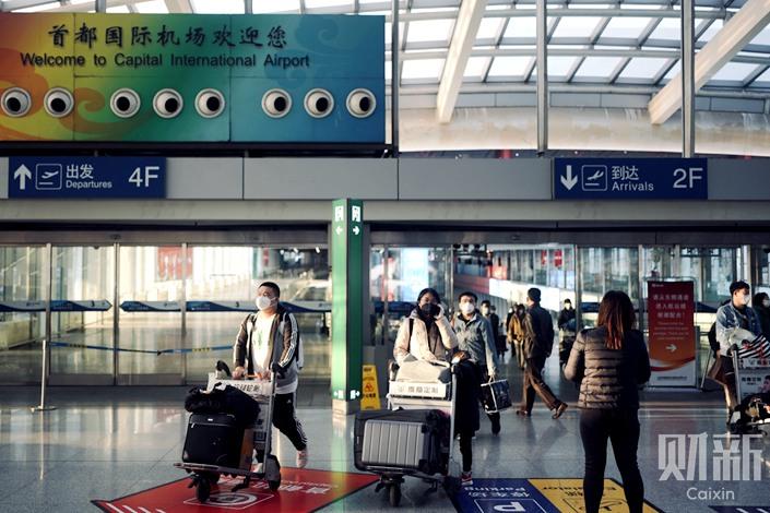 Travelers at Beijing Capital International Airport. Photo: Zhang Hao/Caixin