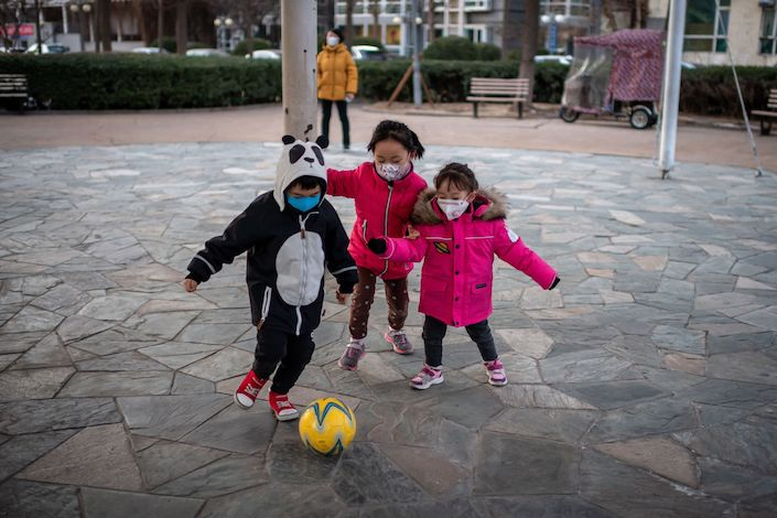 Children wearing protective facemasks play soccer in Beijing on Jan. 29. Photo: Bloomberg