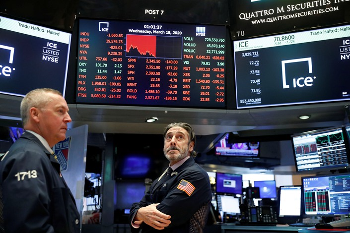 Traders look on after trading was halted on the floor of the New York Stock Exchange (NYSE) on March 18. Photo: VCG