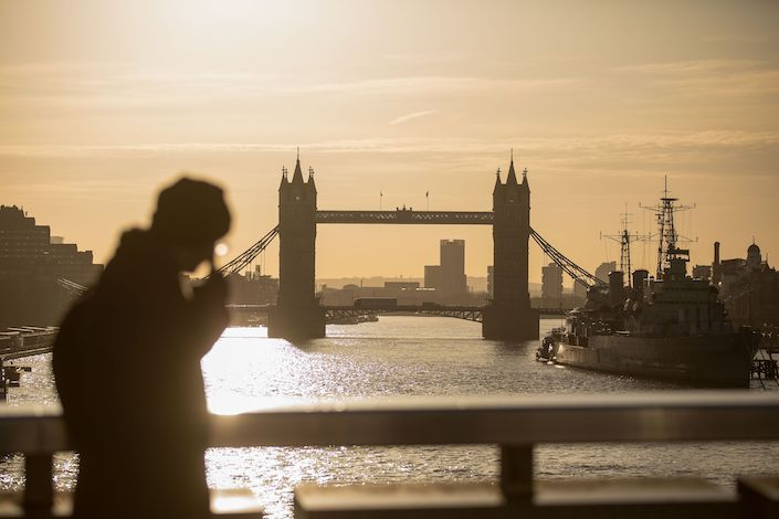 A commuters walk across London Bridge in view of Tower Bridge in London. Photo: Bloomberg