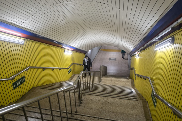 A commuter wearing a protective mask climbs a flight of steps in a subway station in Beijing. Photo: Bloomberg