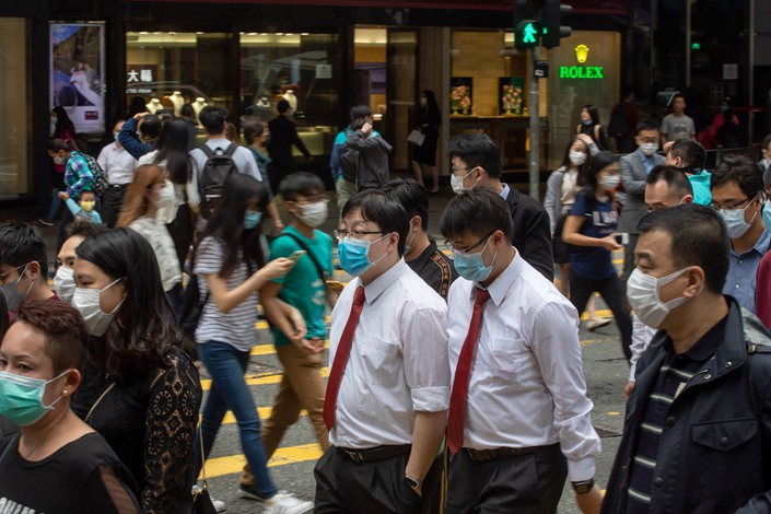 Office workers and pedestrians wearing protective masks walk along Queen's Road Central in the Central district of Hong Kong on March 20. Photographer: Bloomberg