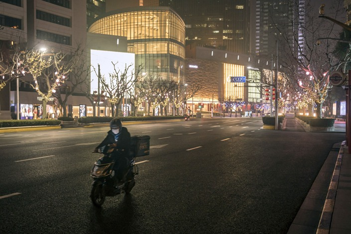A deliveryman wearing a protective mask rides a motorcycle along Nanjing Road in Shanghai on  Feb. 12 Photographer: Qilai Shen/Bloomberg