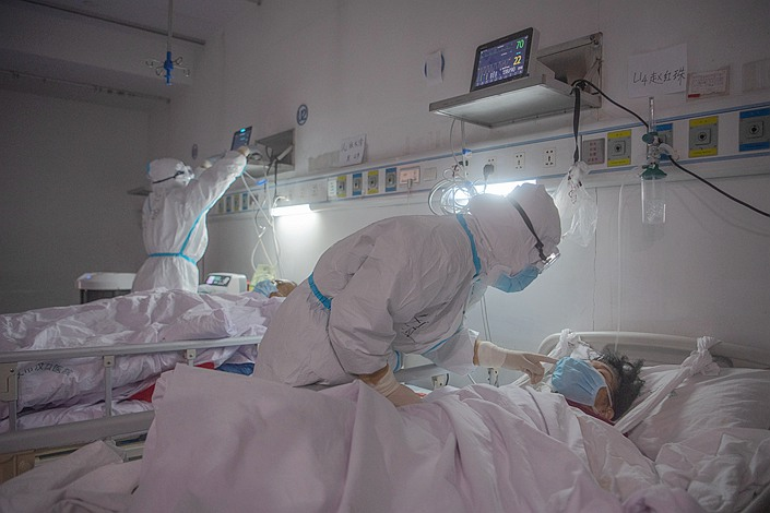 A nurse checks a critically ill Covid-19 patient in Wuhan Hankou Hospital on March 1. Photo: VCG