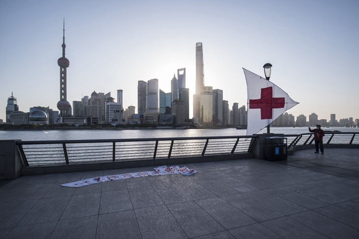 A man flies a kite, marked with a red cross and a message of appreciation to medical professionals, on the Bund as skyscrapers of the Pudong Lujiazui Financial District stand across the Huangpu River during sunrise in Shanghai on March 20. Photo: Bloomberg