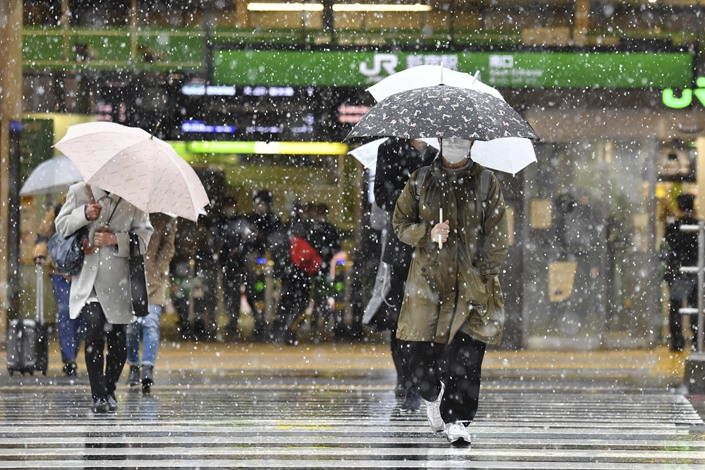 People walk in snow in Tokyo on March 29. Photo: IC Photo