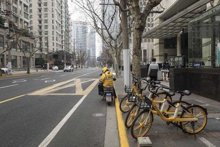 A Meituan Dianping delivery rider waits for a customer outside of an office in Shanghai. Photo: Bloomberg