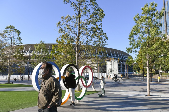 Pedestrians walk past the Olympics rings at the Japan Olympic Museum located in front of the main stadium of the upcoming Olympics in Tokyo on March 24. Photo: Bloomberg