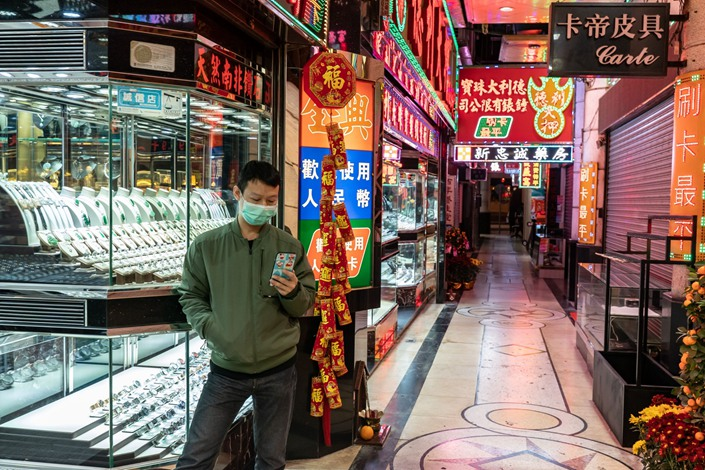 A man stands outside of a jewelry store in a shopping district in Macau on Feb. 4. Photo: Bloomberg