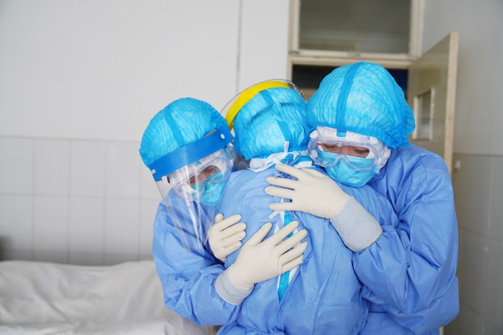Three quarantine nurses embrace on Jan. 28 at a hospital in East China's Shandong province. Photo: People.vcg