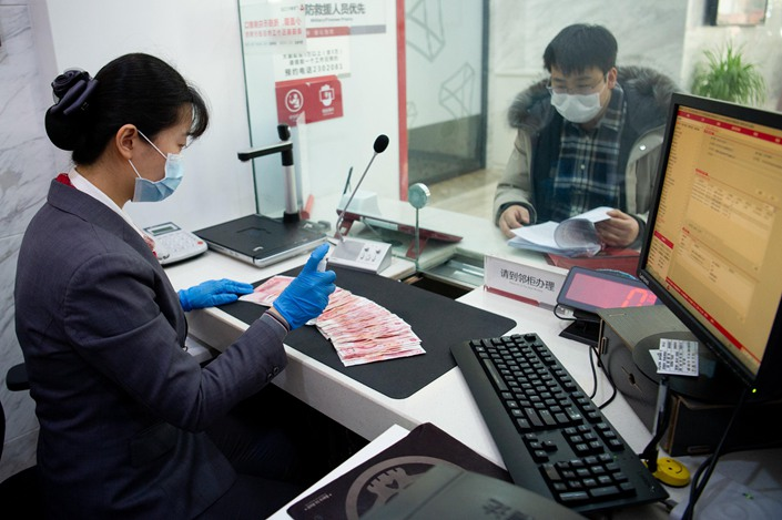 A bank clerk counts cash in Taiyuan, Shanxi province, on March 2. Photo: People.VCG