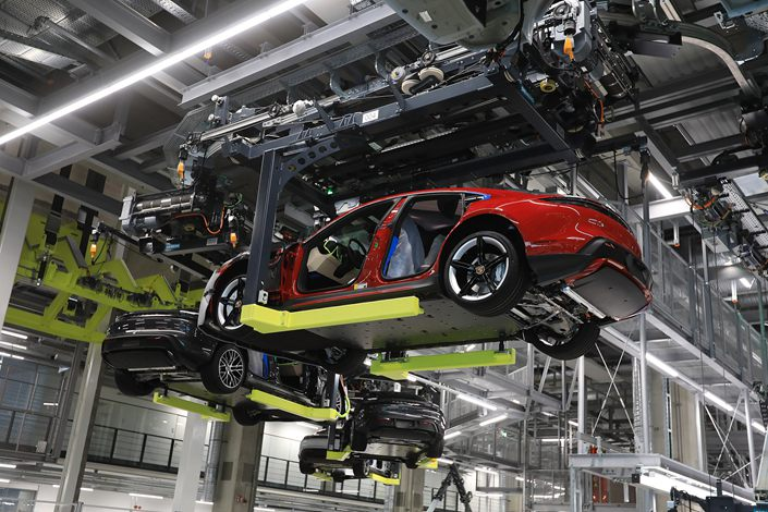 A Porsche Taycan gets lifted at the Porsche AG factory in Stuttgart, Germany, on March 5. Photo: VCG