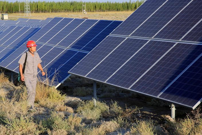 A worker walks past a solar power array in northwestern China on Sept. 11. Photo: VCG