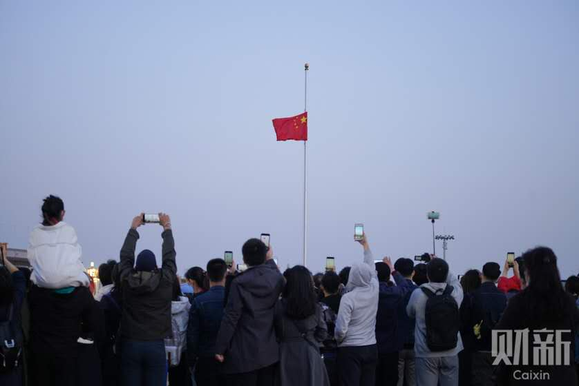 A crowd takes photos of a flag lowered to half-staff during a memorial ceremony for China's Covid-19 victims in Tiananmen Square, Beijing, Apr. 4, 2020. Photo: Caixin