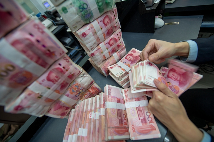 A bank worker counts notes in Haian, Jiangsu province, on April 4. Photo: IC Photo