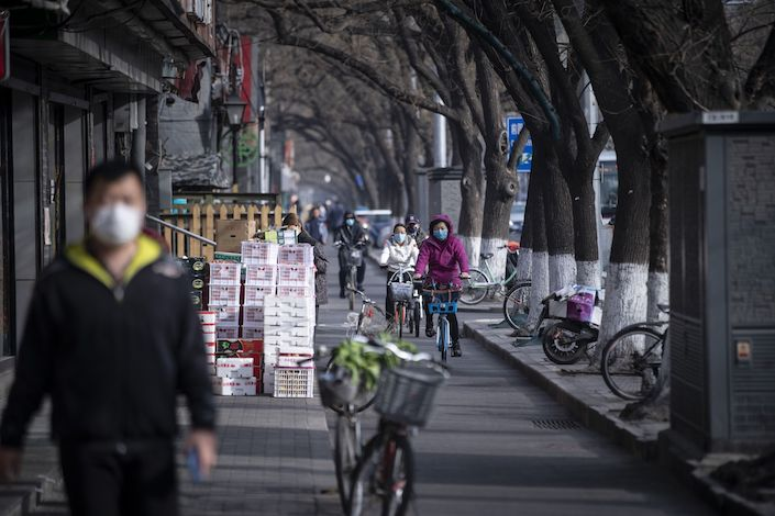 Commuters wearing protective masks ride bicycles down a street in Beijing on March 18. Photo: Bloomberg