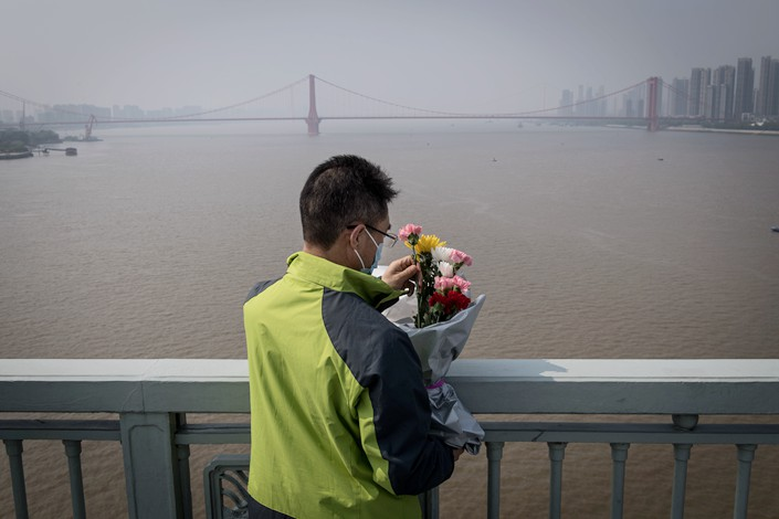 A resident prepares to throw flowers into the Yangtze River from a bridge in Wuhan to honor  the dead on April 4. Photo: IC Photo