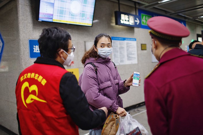 Security guards checks passengers' health codes at a railway station in Wuhan, Central China's Hubei province, on March 28.